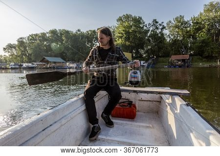 White Mid Age Man Having Troubles With His Old Wooden Oar. He Hates His Paddle And His Outboard Engi