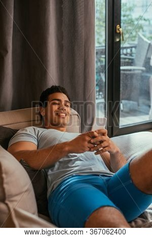 Young Happy Mixed Race Man Chilling And Using Smartphone On Sofa During Quarantine