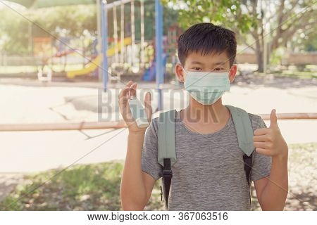 Asian Preteen Tween Boy Wearing Mask And Holding Hand Sanitizer Near Playground, School Reopening, R