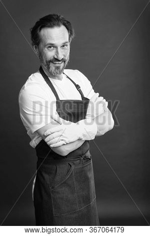He Is Proficient. Happy Housekeeper Red Background. Mature Housekeeper Wear Gloves And Apron. Profes