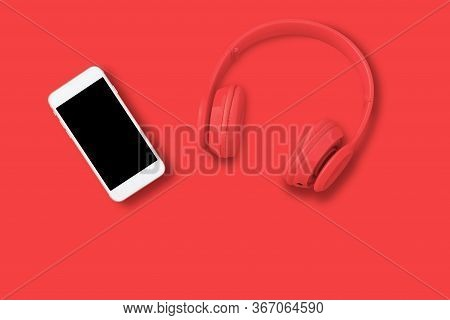 Top View Of Headphones And Smart Phone On Red Background. Minimalist Photo Of Earphones With Smart P