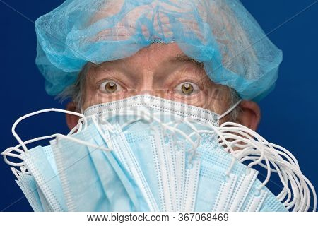 Portrait Of Senior Adult Fearful Glance In Medical Face Mask Covering Nose, Mouth From Sars, 2019-nc