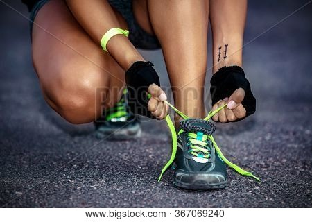 Fit girl ties shoelaces, sporty female on a jogging practice, outdoor workout, happy healthy lifestyle, summer activity