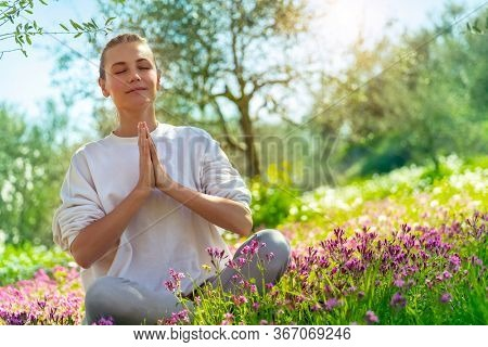 Beautiful woman doing yoga exercise outdoors, nice female in lotus pose meditating with closed eyes in beautiful blooming spring garden, healthy lifestyle, relaxation and wellness concept