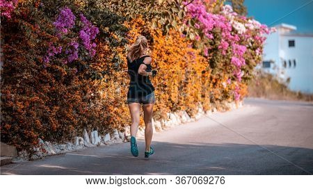 Woman running down the street of blooming flowers, jogging in the countryside, enjoying outdoors workout, happy healthy lifestyle