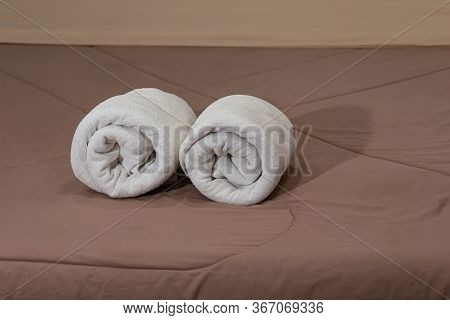 White Bath Towels Roll On A Bed In The Hotel Suite.