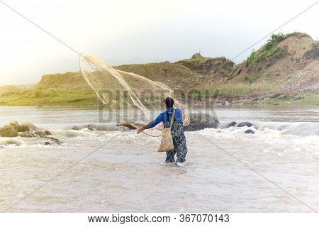 Throwing Fishing Net. Photo Shot Of Water Spatter From Fisherman While Throwing Fishing Net On The R