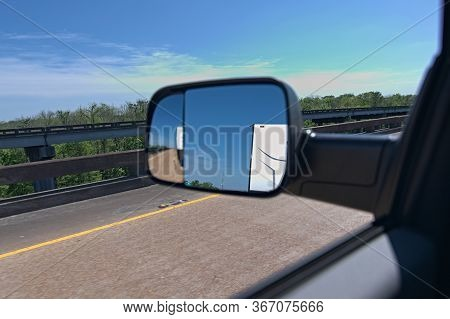Truck Towing Trailer View From Side Mirror. Pulling Rv Down Highway With Diesel Using Tow Mirrors To