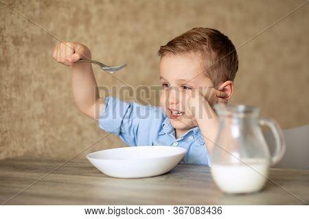 An Adorable European Baby Eats Porridge On His Own. The Boy Does Not Like Porridge. Plays With A Spo