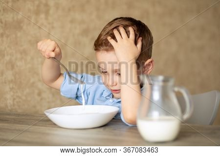 An Adorable European Baby Eats Porridge On His Own. The Boy Does Not Like Porridge. Playing With A S