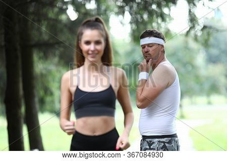 Portrait Of Middle-aged Man Checking Young Beautiful Woman On Morning Run In Park. Attractive Female