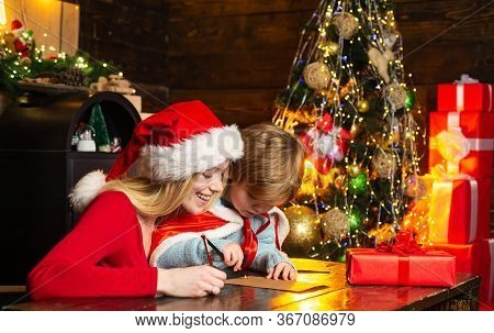 Christmas Child Son And Mother Write Letter To Santa Claus. Lovely Mother Is Writing A Letter To San