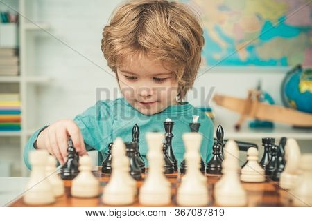 Clever Concentrated And Thinking Child While Playing Chess. Pupil Kid Thinking About His Next Move I