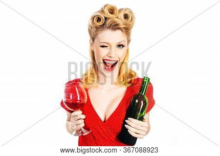 Portrait Of A Smiling Winking Young Woman Holding A Glass Of Red Wine. Beautiful Blond Woman With Re