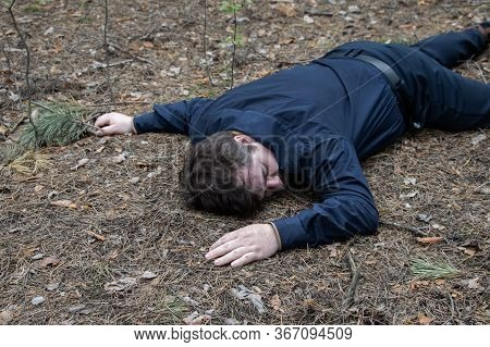 Murder In The Woods. The Body Of A Man In A Blue Shirt And Trousers Lies On The Ground Among The Tre