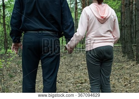 A Man Holds The Hand Of A Teenage Girl In The Woods. The Concept Of Kidnapping And Child Trafficking