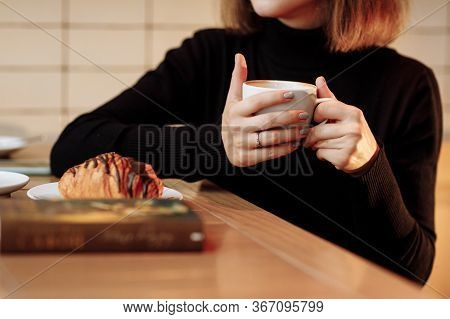 Young Woman Holding In Hands Hot Aroma Coffee Or Tea With Croissant In Breakfast Time At Cafe. Cropp