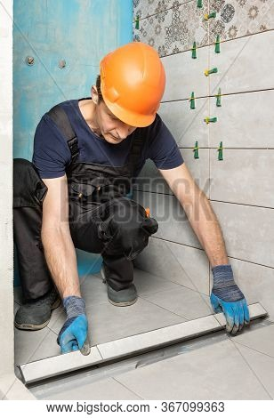 The Worker Is Installing A Drain Lid Decorated With Ceramic Tiles In The Bathroom.