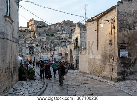 Matera, Italy - September 15, 2019: Tourists During A Walk On Cobblestone Street In The Sassi Di Mat