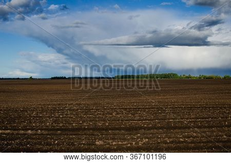 Plowed Field In Agriculture Before Sowing. Spring Landscape With Plowed Field On The Background Of B