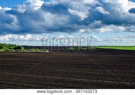 Plowed Field In Spring Time With Blue Sky. Black Plowed Field And Blue Sky With Clouds