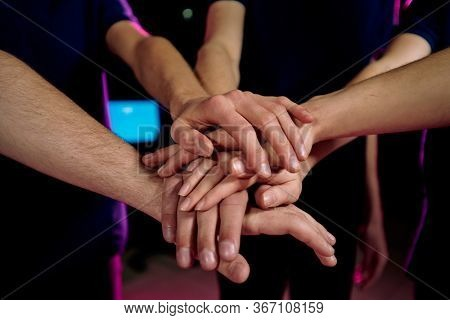 Pile of hands of young contemporary successful cybersports video gamers expressing companionship and togetherness by their gesture