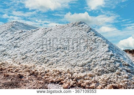 Brine Salt Farm With Blue Sky And White Clouds. Pile Of Organic Sea Salt Near Warehouse. Raw Materia