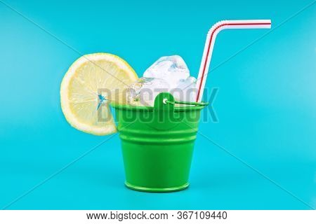 Closeup Of A Green Steel Bucket With Ice Cubes, Lemon Slice And A Straw On A Vivid Blue Background.