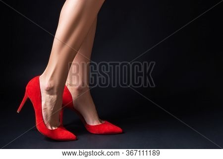 Women's Red Shoes On A Black Background Close-up. Pumps On The Feet. Minimalism Luxury Shoes Concept