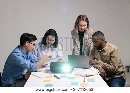 Multi-ethnic group of young contemporary analysts or financiers brainstorming and discussing new ideas for presentation at meeting