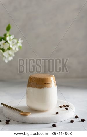 Trendy Dalgona Coffee In A Glass With Whipped Foam On Gray Background With Coffee Beans. Iced Whippe