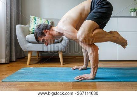 Man In Bakasana Pose Doing Vinyasa Yoga Flow