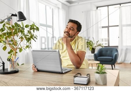 technology, remote job and business concept - thinking indian man with laptop computer working at home office
