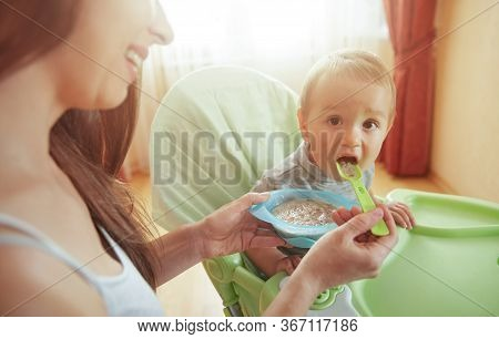Happy Smiling Mom Feed Son Sitting In Highchair With Food. Little Baby Eating Food Tasty Porridge Mi