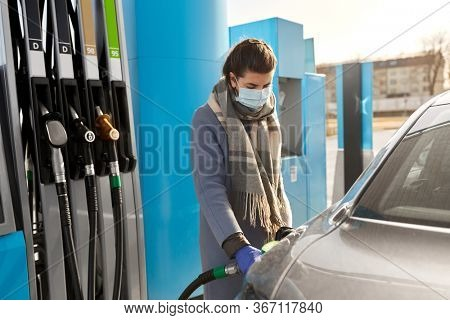 health, safety and pandemic concept - young woman wearing protective medical mask and gloves filling her car with gasoline at gas station