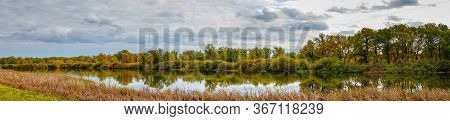 Panorama Overcast Clouds Over A Small Forest Lake In Front Of A Beautiful Autumn Forest. Autumn Land