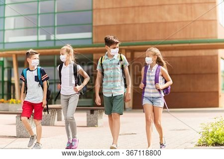 education, healthcare and pandemic concept - group of elementary school students wearing face protective medical masks for protection from virus disease with backpacks walking and talking outdoors