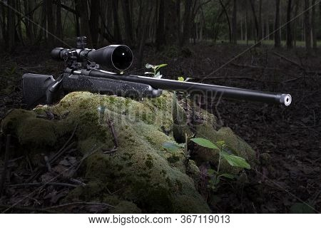 High Powered Rifle With A Scope In A Forest With Room For Text