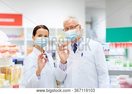 medicine, pharmaceutics and healthcare concept - happy smiling apothecaries wearing face protective medical masks for protection from virus disease at pharmacy showing ok hand sign