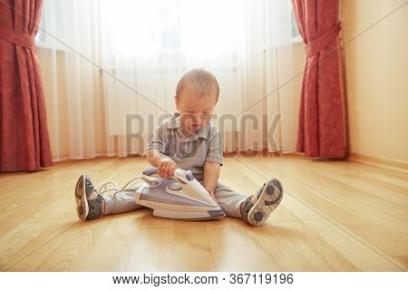 Little Baby Boy With Iron Sitting On Room Floor At Home. Young Parent Helper. Interested Cute Toddle