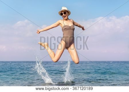 Young Adult Bald Shaved Hair Hipster Beautiful Caucasian Female Person In Swimsuit Hat And Sunglasse