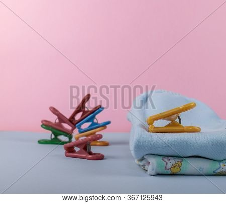 Children's Clothing After Washing Machine. Iron Clothes Folded In A Pile Of Clothing & Soft Pink Bac