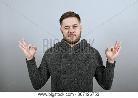 Young Bearded Dark Haired Man In Black Stylish Shirt On Gray Background, Confident Male Raised Hands