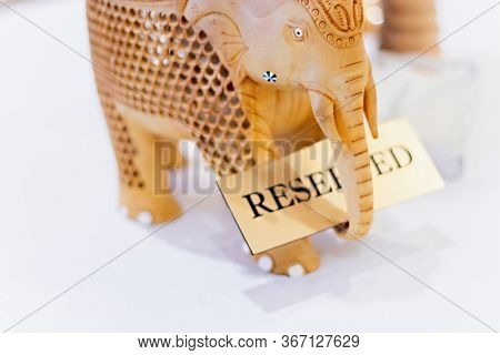Decorative Figure Of Wooden Indian Elephant On Table With Sign Reserved. Concept Table Is Reserved,