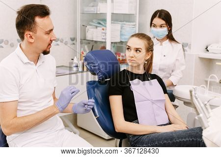 A Beautiful Girl Sits In The Dentists Chair And Listens To The Doctor And His Assistant. Dentist App