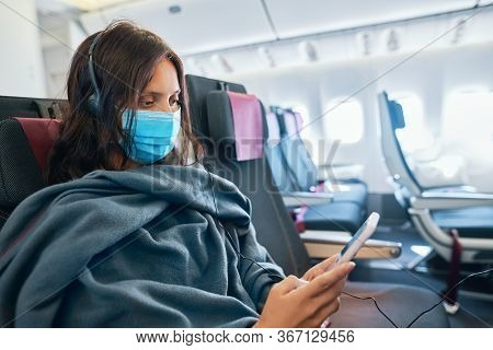 Woman In Virus Protection Face Mask Using Smartphone Sitting In Empty Airplane . Covid-19 Evacuation