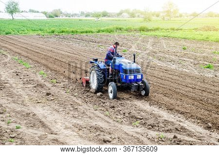 A Farmer On A Tractor Cultivates A Farm Field. Soil Milling, Crumbling And Mixing. Agroindustry, Far