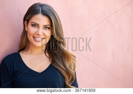 Outdoor Head And Shoulders Portrait Of Attractive Young Woman Leaning Against Wall In The Street