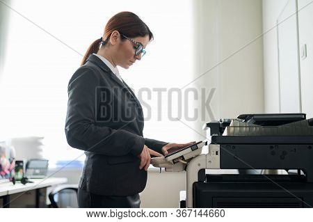 Business Woman In A Suit And Glasses Makes Copies Of Documents On A Photocopier. Female Office Manag