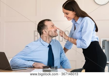 Businesswoman Seducing Male Employee Flirting Touching His Face At Workplace In Modern Office. Sexua